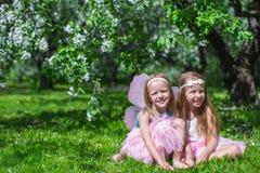 Kleine aanbiddelijke meisjes met vlindervleugels in Stock Afbeeldingen