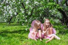 Kleine aanbiddelijke meisjes met vlindervleugels in Stock Foto's