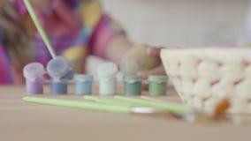 Kleine Acrylfarbenflaschen und -bürsten, die auf dem Tisch nah oben liegen Hände des kleinen Mädchens setzten die Bürste in e stock video