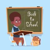 Kleine Afroamerikaner-Schuljungen-Sit At Desk Over Class-Brett-Schüler-Bildungs-Fahne Stockbild