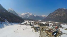 Kleine Alpiene toevluchtstad bij oever van het meer, reusachtige bergen, sneeuwpieken, snelle motie stock footage