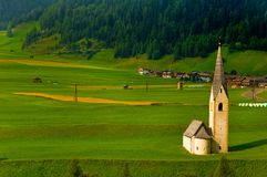 Kleine alpine Kirche auf dem grünen Gebiet Stockfoto