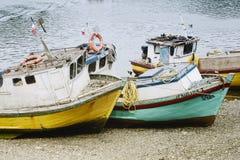 Kleine alte Fischerboote auf dem Strand in Puerto Montt Stockbilder