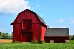 Kleine alte zweistöckige rote Scheune mit Anhang unter sonnigen blauen Himmeln an einem heißen und feuchten Sommertag Stockbild