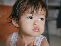 Kleine asiatische Babylippen bedeckt mit Ei, während sie lernt, gekochtes Ei durch zu essen stockfotografie