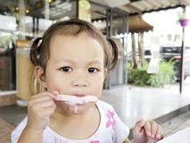 Kleine asiatische Mädchen des selektiven Fokus ist glücklich, eine köstliche Eiscreme, Kopienraum zu essen lizenzfreie stockbilder