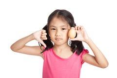 Kleine asiatische Mädchendaumen unten mit einem Ei in der Hand lizenzfreie stockbilder