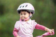 Kleine asiatische Mädchenfahrt das Fahrrad Lizenzfreie Stockbilder