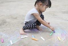 Kleine asiatische Mädchenzeichnung mit Kreide auf dem Bürgersteig Lizenzfreies Stockbild