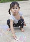 Kleine asiatische Mädchenzeichnung mit Kreide draußen Stockfoto