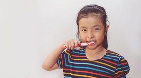 Kleine asiatische nette M?dchenb?rstenz?hne lizenzfreie stockfotografie