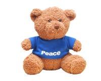 Kleine Bärnabnutzung ein blaues Hemd lokalisiert mit weißem Hintergrund Schriftliches Wort Frieden am Hemd Lizenzfreie Stockbilder