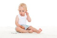 Kleine baby die aan muziek luisteren. Stock Foto's