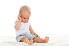 Kleine baby die aan muziek luisteren. Stock Afbeelding