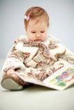 Kleine baby die een boek leest Stock Afbeeldingen