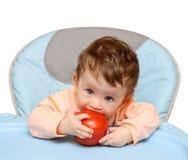 Kleine baby het bijten tomaat Stock Foto