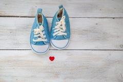 Kleine Babyblauturnschuhe auf einem weißen hölzernen Hintergrund Roter Schuh Stockfoto