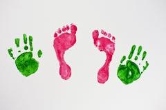Kleine Babyfüße und -hände Stockfotos