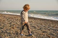 Kleine babyjongen die de kust lopen de jongensgangen bij zonsondergang op het strand royalty-vrije stock afbeelding