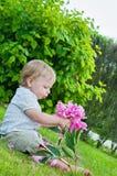 Kleine babyjongen die roze bloem in zijn hand houden Stock Afbeelding
