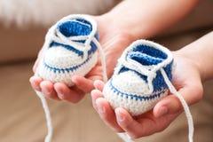 Kleine Babyschuhe Handgestrickte erste Turnschuhe auf den Händen des Vatis Stockfoto