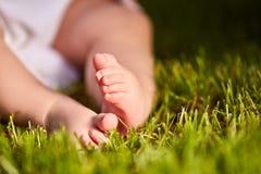 Kleine babyvoeten op het groene gras bij de zomer sunshiny dag in het park royalty-vrije stock foto's