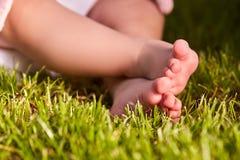 Kleine babyvoeten op het groene gras bij de zomer sunshiny dag in het park royalty-vrije stock afbeelding