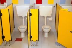 Kleine badkamers van een school voor kinderen met watercloset Stock Foto's