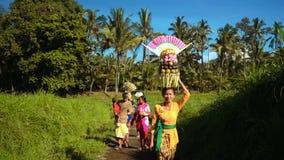 Kleine Balinese optocht met dienstenaanbod tussen padievelden stock footage