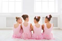 Kleine ballerina's die in balletstudio spreken stock afbeeldingen