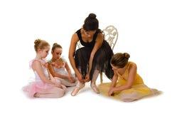 Kleine Ballerinen lernen, Pointe-Schuhe zu binden Lizenzfreies Stockfoto