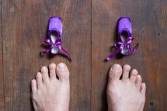 Kleine Ballettschuhe und große Füße Lizenzfreie Stockbilder