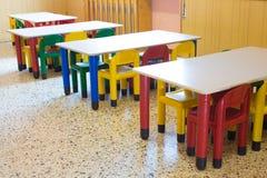 Kleine banken en kleine gekleurde stoelen in kleuterschool Royalty-vrije Stock Fotografie
