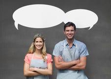 Kleine bedrijfseigenaarpaar met toespraakbellen die zich tegen grijze achtergrond bevinden Stock Afbeelding