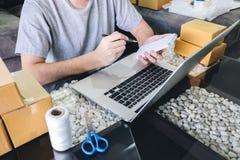 Kleine bedrijfspakket voor verzending aan cli?nt thuis, de Jonge freelance mens die van het ondernemersmkb met vakje van de nota  royalty-vrije stock afbeeldingen
