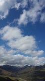 Kleine Berge unter großem Himmel und Wolken Stockfotos