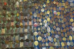 Kleine Bilder von Buddha und von Mönchen auf Stein- und Metallamuletten für Verkauf auf Straßenmarkt Stockbild