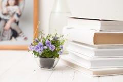 Kleine blühende Blumen auf einem weißen Holztisch Stockbild