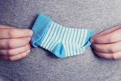 Kleine blaue Socke für das ungeborene Baby im Bauch der schwangeren Frau Hände der glücklichen Frau wenig Socke des Kindes halten stockbild