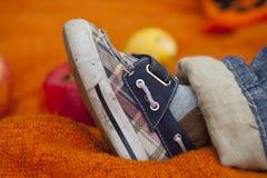Kleine blaue und weiße Turnschuhe auf dem Fuß des Babys Lizenzfreies Stockfoto