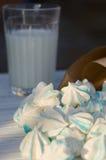 Kleine blaue Zuckerplätzchen und ein Glas Milch Stockfotografie