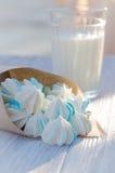 Kleine blaue Zuckerplätzchen und ein Glas Milch Stockfotos
