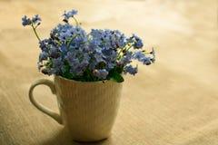 Kleine blauwe bloemen in een witte kop op de lijst stock afbeelding