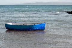 Kleine blauwe die het roeien boot in het overzees wordt vastgelegd royalty-vrije stock foto's
