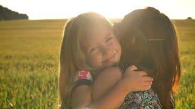 Kleine blonde junge Mutter umarmende und, schönes Weizenfeld während des Sonnenuntergangs im Hintergrund lächelnde Tochter stock footage