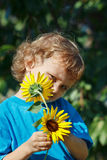 Kleine blonde Jungenholdingsonnenblume an einem sonnigen Tag Lizenzfreie Stockbilder