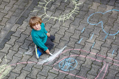 Kleine blonde Jungenmalerei mit bunten Kreiden draußen Stockfoto