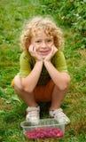 Kleine blonde Jungensammelnhimbeeren im Garten Stockfotografie