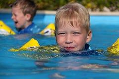 Kleine blonde Jungenschwimmen im Pool Lizenzfreie Stockfotos
