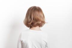 Kleine blonde kaukasische Mädchenrückseite über weißem Hintergrund Lizenzfreie Stockbilder